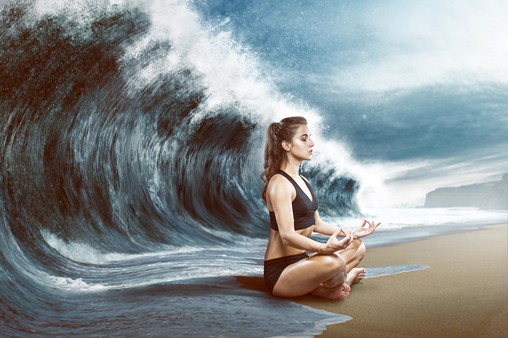 Eine Frau enstpannt sich vor einer großen Welle